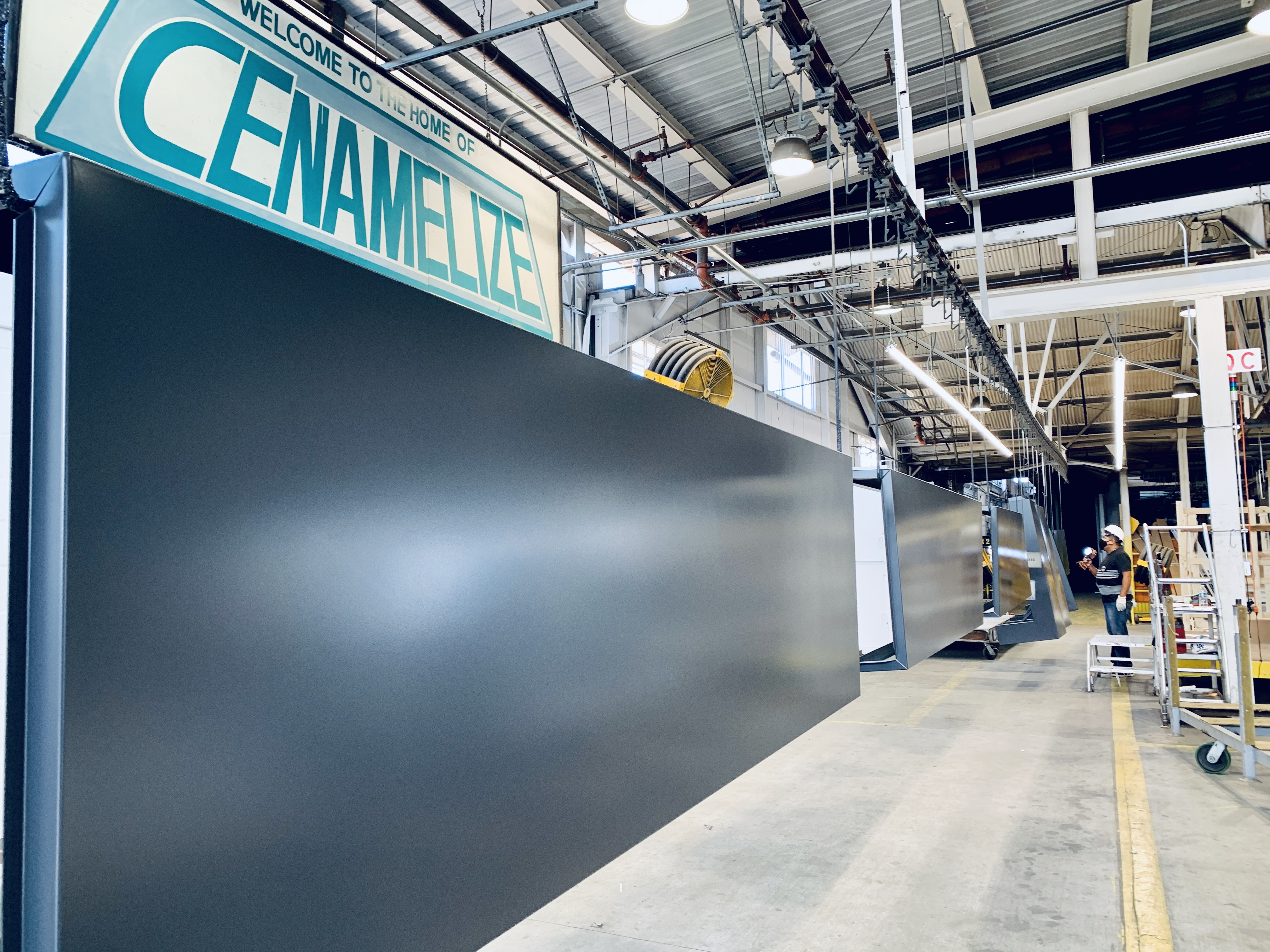 "The interior of the Certified Enameling, Inc. facility with a sign that says, ""Welcome to the home of Cenamelize"""